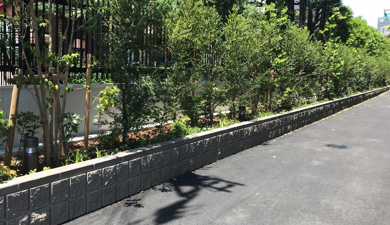 緑豊かな植栽を囲う割肌ブロック-REリブスクエア